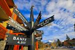 Stock photo of Multi-directional metal post sign and white letters showing various mountains of Banff National Park in Alberta, Canada.