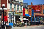 Stock photo of a colorful cafe/restaurant street scene at the Byward Market in the City of Ottawa, Ontario, Canada. People are seen dining at outside tables surrounded by shops on this busy street.