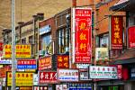 Stock photo of colorful street signs spanning several buildings on a street in the Chinatown section of the city of Toronto in Ontario, Canada.