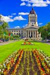 Stock photo of the Legislative Building with a bright green lawn and large colourful flower beds. Above and behind the building is a vivid blue sky with some well defined pure white clouds.