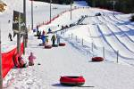 Stock photo of people walking up to the magic carpet lift with their tubes at the Coca-Cola Tube Park on Blackcomb Mountain, Whistler Blackcomb, Whistler, British Columbia, Canada.