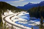 Stock photo of winding railway tracks beside the snow and ice fringed Bow River during winter, Banff National Park, Canadian Rocky Mountains, Alberta, Canada.