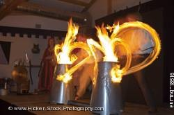 Entertainers drumsticks lit by fire medieval feast