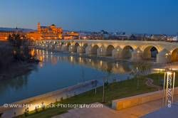 Puente Romano bridge spans Rio Guadalquivir to Mezquita at dusk in City of Cordoba Andalusia