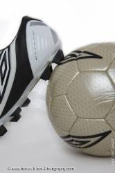 Soccer shoe leaning against a soccer ball