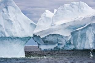 Stock photo of two blue large icebergs floating in Iceberg Alley, an arctic scene captured while iceberg watching in the waters off the Great Northern Peninsula, Northern Peninsula, Newfoundland, Canada.