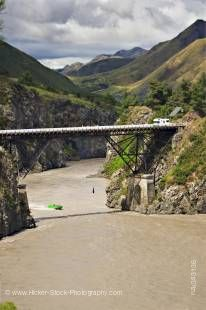 A jet boat speeds to pick up a Bungee Jumper shown hanging from the Waiau Ferry Bridge over the Waiau River and Thrill Seekers Canyon near Hanmer Springs, South Island, New Zealand.