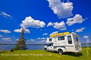 Stock photo of a camper with a view of Lake Audy at the Lake Audy Campground in Riding Mountain National Park, Manitoba, Canada.