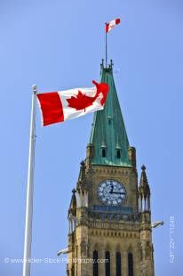 Stock photo of a Canadian flag in front of the upper part of the Peace Tower on Parliament Hill, Ottawa, Canada