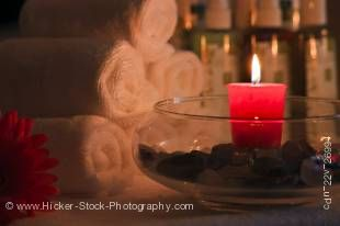Stock photo of a closeup of a round glass bowl with a vivid red candle sitting on a tabletop.