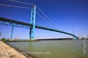 Stock photo of large bulk carrier ship passing under Ambassador Bridge expanding the Detroit River from Windsor, Ontario Canada to Detroit, Michigan, United States