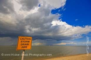Stock photo of a yellow caution sign on the sandy shores of Lake Winnipeg with threatening clouds above in the town of Winnipeg Beach, Manitoba, Canada.