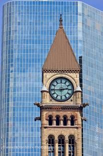 Stock photo of the Clock tower at the old City Hall building in downtown Toronto, Ontario Canada. the top portion of the clock tower is seen with its row of three tall arched windows above a row of four smaller windows in the sand colored stone of the edi