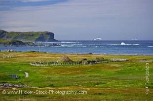 Stock photo of view from the Information Centre at L'Anse aux Meadows National Historic Site of Canada and UNESCO World Heritage Site, over the sod huts of the site towards icebergs in Iceberg Alley and the Atlantic Ocean coastline, Northern Peninsula, Gr