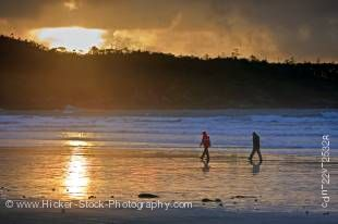 Stock photo of a couple walking along the beach at Cox Bay near Tofino during sunset on the west coast of Vancouver Island in British Columbia, Canada.