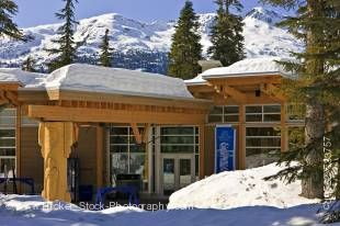 Stock photo of the Day Lodge at the Whistler 2010 Olympic Park Nordic Sports Venue in Callaghan Valley, British Columbia, Canada. Deep snow covers the ground, the lodge, and the mountains above in this winter scene that also includes several tall evergree