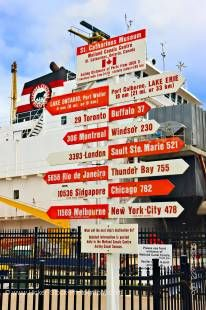 Stock photo of red and white sign post pointing towards various destinations around the world at the St Catharine's Museum, Lock 3, Welland Canals Centre, St. Catharine's, Ontario, Canada.