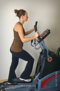 Stock photo of a woman working out on an elliptical trainer in the exercise room at the Black Bear Resort & Spa, Port McNeill Northern Vancouver Island, Vancouver Island, British Columbia, Canada.
