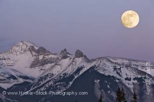 Stock photo of a full moon at dusk shining over the snowcapped Fairholme Range during winter, as seen from 2nd Vermilion Lake near the town of Banff in Banff National Park, Canadian Rocky Mountains, Alberta, Canada.