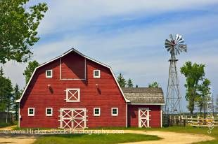 Stock photo of the Farm Barn at the Mennonite Heritage Village in Steinbach, Manitoba, Canada, on a sunny day against a blue sky heavily streaked with white clouds