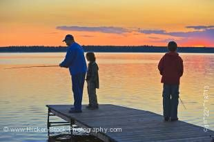 Stock photo of a father with his two sons fishing at the end of a wharf on Lake Audy at sunset, Riding Mountain National Park, Manitoba, Canada.