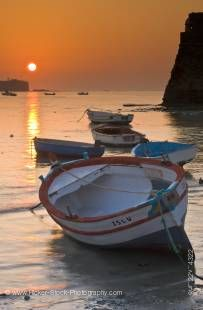 Stock photo of a small fishing boat at a golden sunset on the Playa de la Caleta in Cadiz, Spain.