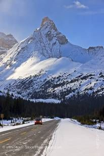 Stock photo of a smart car alone on a snowy road, the Icefield Highway and dwarfed by Hilda Peak as viewed from the Icefields Parkway in Banff National Park, Canadian Rocky Mountains, Alberta, Canada.