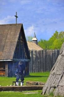 Stock photo of historically dressed character tending a fire in the Native Area of the Sainte-Marie among the Hurons complex in the town of Midland, Ontario, Canada.