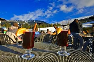 Stock photo of glasses of hot gluehwein (mulled wine) served at the Longhorn Saloon and Grill an apres-ski bar at the base of Whistler Mountain, Whistler Village, British Columbia, Canada. A bright blue sky with few clouds provides a lovely background to