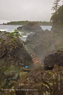 Stock photo of people bathing in the rocky pools of the geothermal hot springs at Hot Springs Cove, Openit Peninsula, Maquinna Marine Provincial Park, Clayoquot Sound, Clayoquot Sound UNESCO Biosphere Reserve, West Coast, Vancouver Island, British Columbi