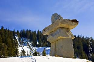 Stock photo of a Large stone inukshuk - Ilanaaq (the Vancouver 2010 Olympic Winter Games emblem) at the entrance to the Whistler Olympic Park Nordic Sports Venue, with the Olympic Ski Jumps and blue sky in the background, Callaghan Valley, British Columbi