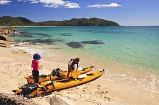 Stock photo of Kayakers on the beach at Arch Point, Abel Tasman National Park, Tasman District, South Island, New Zealand.