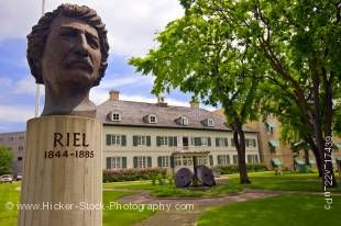 Stock photo of a monument showing a head bronze of Louis A Riel and the Saint Boniface Museum in Winnipeg, Manitoba, Canada.