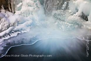 Stock photo of a partially frozen Lower Falls of the Johnston Creek during winter with water flowing into a pool at the base, surrounded by ice formations, Johnston Canyon, Banff National Park, Canadian Rocky Mountains, Alberta, Canada.