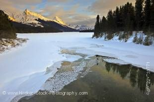 Stock photo of the partially frozen Maligne River as it drains from Maligne Lake during winter with a view towards the snow capped mountains of Leah Peak (2810 metres/9220 feet) and Samson Peak (3077 metres/10095 feet) during sunset, Maligne Lake Road, Ja