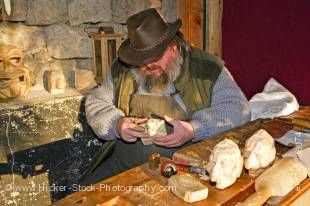 Stock photo of a bearded man carving the heads of puppets at the Christmas Markets at the Hexenagger Castle, Hexenagger, Bavaria, Germany, Europe.