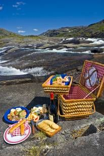 Stock photo of a wicker picnic hamper beside a waterfall with a helicopter in the background in the Mealy Mountains, Southern Labrador, Labrador, Newfoundland Labrador, Canada.