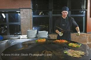 Stockphoto of a chef performing with utensils while preparing meals at the Mongolie Grill World Famous Stirfry Restaurant in Whistler Village, British Columbia, Canada.