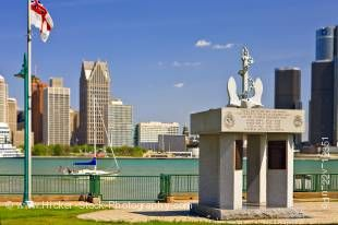Stock photo of navy memorial in Dieppe Gardens, the Detroit River and the skyline of Detroit, Michigan in the background.