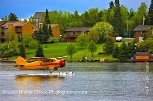 Stock photo of a bright orange Norseman aircraft taxiing on the water in the town of Red Lake, Ontario, Canada. The shore of the lake across the water has many beautiful trees and some brick buildings under a bright blue sky.
