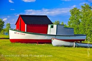 Stock photo shows two old boats and a bright red shed in Hecla Village on the shores of Lake Winnipeg, Hecla Island, Manitoba, Canada.
