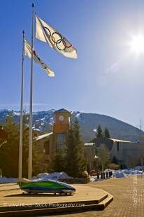 Stock photo of Olympic flags and the Vancouver 2010 bobsled displayed outside the Winter Olympic Office along the Village Stroll next to the BrewHouse in Whistler Village, with Blackcomb Mountain in the background, British Columbia, Canada. This photo was