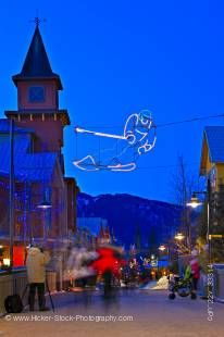 Stock photo of decorative lighting and pedestrian activity along the Village Stroll at dusk, Whistler Village, British Columbia, Canada. The sky above is a gorgeous deep blue over this active Winter scene showing people moving about and a skier made of li