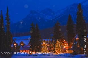 Stock photo of a winter night scene of the Post Hotel located on the snow covered banks of the Pipestone River, Lake Louise, Banff National Park, Canadian Rocky Mountains, Alberta, Canada.