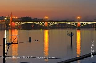 Stock photo of the lighted Puente de Isabel II Bridge across the Rio Guadalquivir River at dusk, City of Sevilla, Province of Sevilla, Andalusia, Spain, Europe.