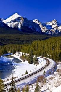 Stock photo of railway tracks beside the snow and ice fringed Bow River during winter with Fairview Mountain and blue sky in the background, Banff National Park, Canadian Rocky Mountains, Alberta, Canada.