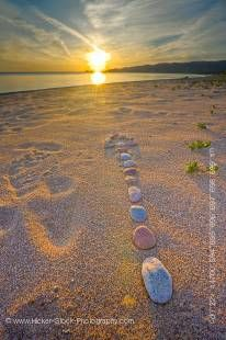 Stock photo of a rock design in the shape of an arrow pointing toward the setting Sun on the beach at Agawa Bay in Lake Superior Provincial Park, Ontario, Canada.