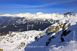 Stock photo of the view from Roundhouse Lodge on Whislter Mountain looking toward Blackcomb Mountain at the Whislter Blackcomb ski resort in Whistler, British Columbia, Canada. Under a bright blue sky streaked with wispy clouds, both mountains are heavily