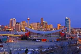 Stock photo of the Saddledome with high-rise buildings and the Calgary Tower in the background at sunrise, City of Calgary, Alberta, Canada.