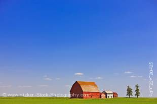 Stock photo of red barns in the middle of a large flat field in the prairie land of southern Saskatchewan, Canada.